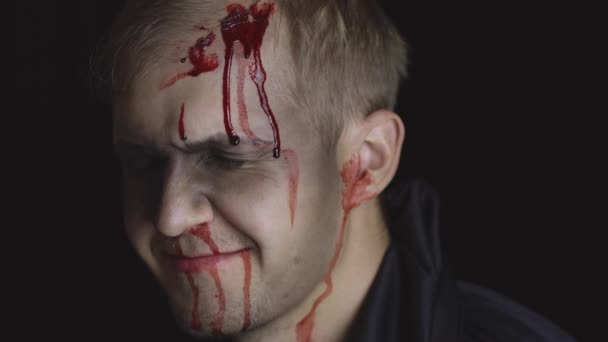 Halloween man portrait. Guy with dripping blood on his face. Scary makeup