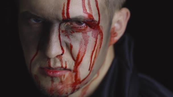 Portrét Halloweena. Chlápek s kapající krví na tváři. Děsivý make-up