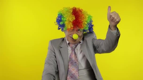 Idősebb bohóc üzletember, parókás szabadúszó mutogatja a hüvelykujját. Halloweeni