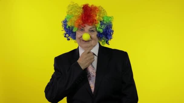 Idősebb bohóc üzletasszony főnök parókában igazítja a nyakkendőt. Sárga háttér