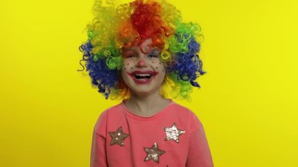 Kislány bohóc szivárvány parókában, buta arcokat vágva. Szórakozni, mosolyogni, nevetni. Halloweeni