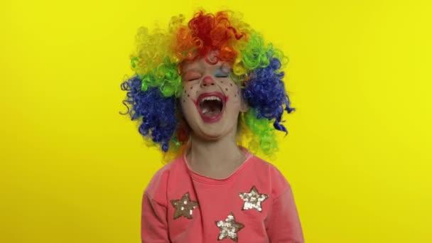 Gyermek bohóc szivárvány parókában, buta arcokat vágva. Szórakozom, mosolygok. Fel a hüvelykujjal. Halloweeni