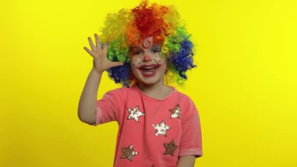 Egy kislány bohóc, színes parókában, buta arcokat vágva. Jól mutatja a jelet, mosolyog. Halloweeni