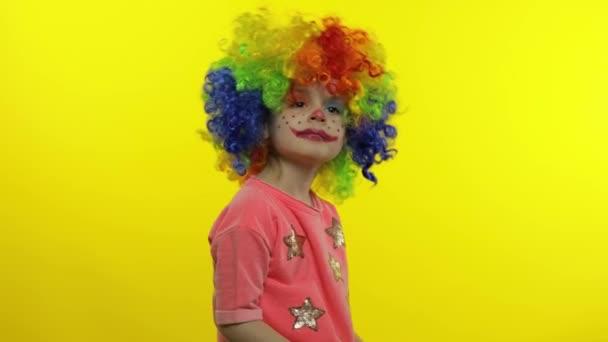 Kislány bohóc szivárvány parókában, integet, szórakozik, mosolyog. Halloweeni