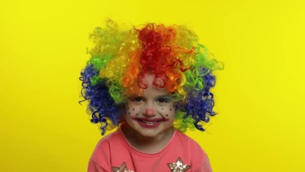 Egy kislány bohóc, színes parókában, buta arcokat vágva. Szórakozni, mosolyogni, nevetni. Halloweeni