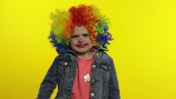 Dühös kislány bohóc színes parókában, gonosz arcokat vágva. Öklöt mutat. Halloween van. Kifejezések