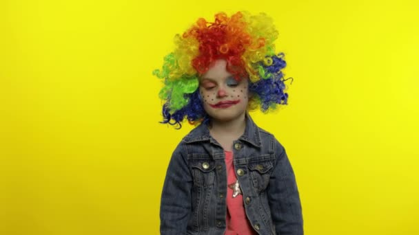 Egy kislány bohóc színes parókában. A készpénz dollárból származó jövedelem felülről esik