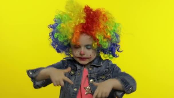 Egy kislány bohóc, színes parókában, buta arcokat vágva. Szórakozni, mosolyogni, táncolni. Halloweeni