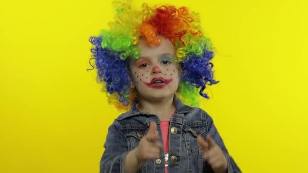Malá holčička klaun v duhové paruce dělat hloupé obličeje. Bavíš se, usmíváš se, tancuješ. Halloween