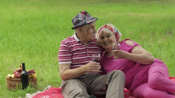 Familienpicknick am Wochenende im Park. Aktives Senioren-Ehepaar sitzt auf Decke und trinkt Wein