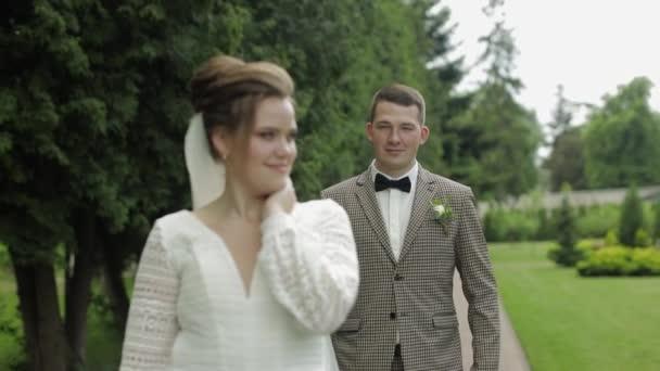 Novomanželé. Bělošský ženich s nevěstou procházející se v parku. Svatební pár. Muž a žena v lásce