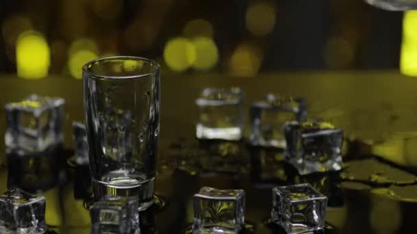 Barmann gießt gefrorenen Wodka aus der Flasche in Schnapsglas. Eiswürfel vor goldglänzendem Partyhintergrund