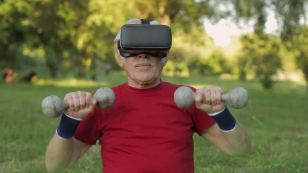 Älterer Großvater mit VR-Headset-Helm macht Fitnessübungen mit Kurzhanteln im Park