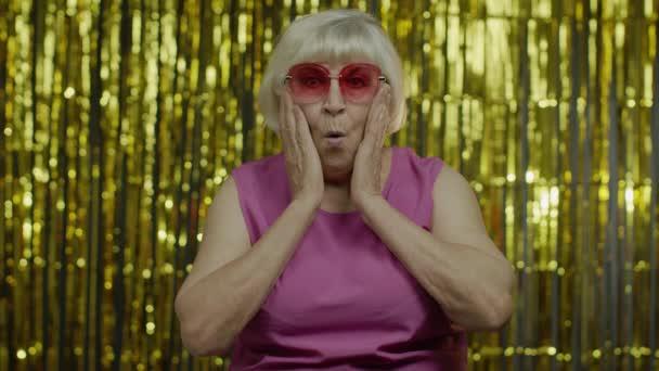 Portrét vzrušené starší ženy, dívající se na kameru, užasle otvírající ústa