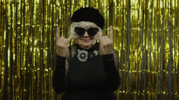 Izgatott pozitív idős nő mutatja rock and roll gesztus és őszintén mosolyog, mutató nyelv