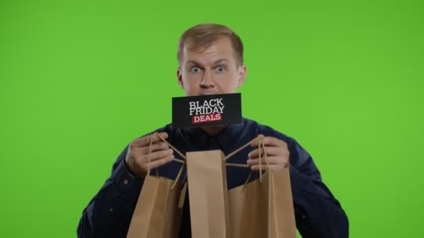 Surprised man showing shopping bags and Black Friday Deals inscription in his mouth. Chroma key