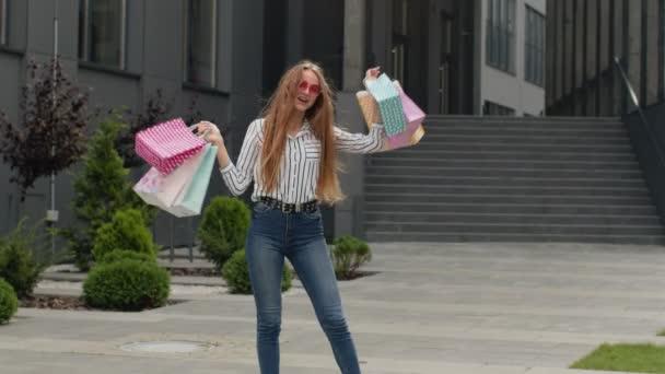 Stílusos lány bevásárlószatyrokkal, örvendező kedvezmények az üzletben, tánc, ünneplés. Fekete péntek