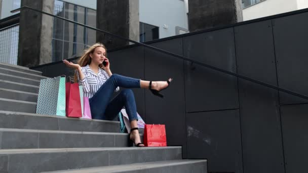 Girl sitting on stairs with bags talking on smartphone about sale in shopping mall in Black Friday