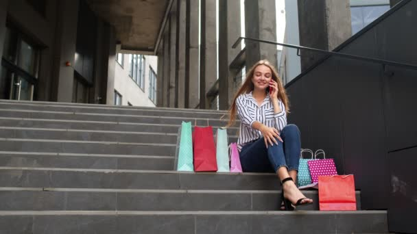 Girl sitting on stairs with bags talking on mobile phone about sale in shopping mall in Black Friday
