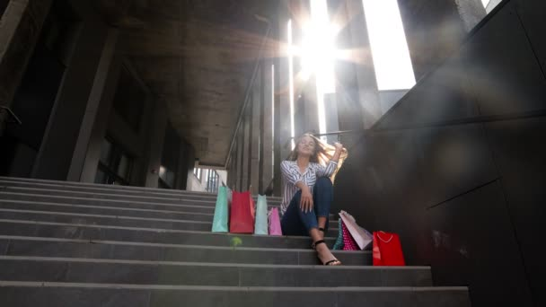 Teenager smiling girl with shopping bags sitting on stairs near shopping mall. Black Friday sale