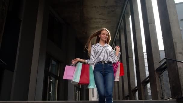 Usmívající se dívka chůze od centra obchoďáku s nákupními taškami, šťastný s nákupem na Černý pátek