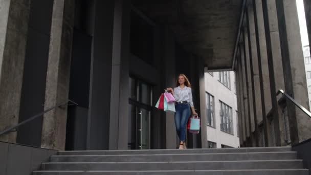 Dívka s nákupními taškami, spining, tanec, vypadá spokojeně s nákupem, těší cenové slevy