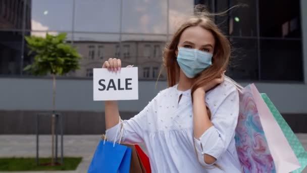 Dívka v ochranné masce s nákupními taškami ukazující nápis slova prodeje během pandemie covid-19
