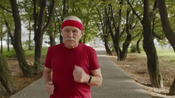Männlicher Senior läuft im Park die Straße entlang. Reifer Läufer trainiert, hört Musik