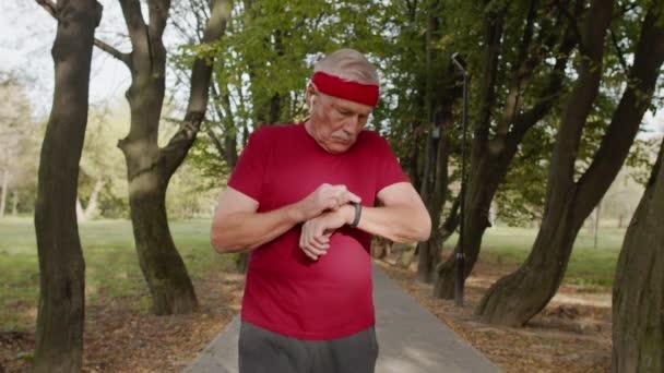 Senior alter Mann läuft im Park und nutzt Smart Watch, Tracking-Ergebnis nach Fitness-Training