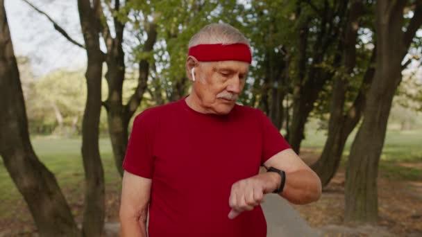 Senior Sport Runner Mann mit Smart Watch tippt Touchscreen, Tracking-Ergebnis nach Fitness-Training
