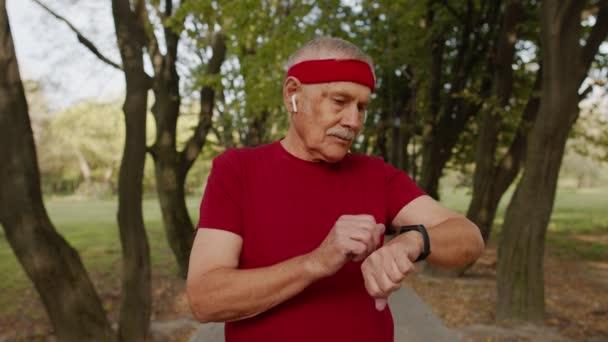 Senior Läufer Mann im Park mit Smartwatch, Tracking-Entfernung, Puls nach Fitness-Training überprüfen