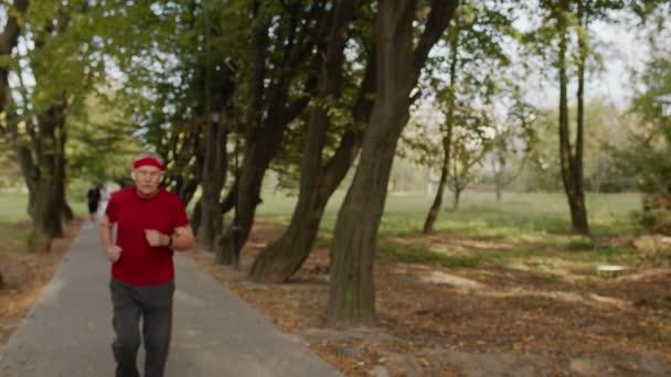 Älterer Sportler hört nach dem Laufen auf, benutzt Smart Watch, überprüft die Herzfrequenz während der Fitness