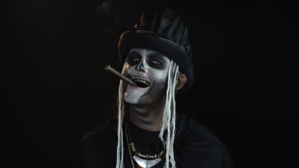 Gruseliger Mann im Skelett-Halloween-Cosplay-Kostüm, Zigarre rauchend, Gesichter machend, lächelnd
