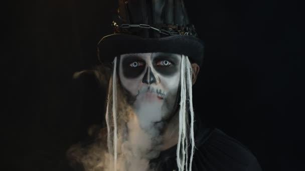 Gruseliger Mann in gruseligem Skelett-Halloween-Cosplay atmet Zigarettenrauch aus dem Mund
