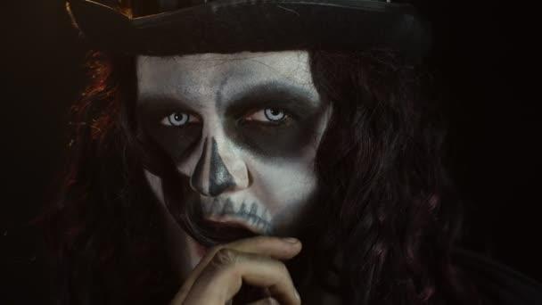 Strašidelné dlouhé vlasy muž s kostrou make-up dělat obličeje a ukazuje na kameru, snaží se vystrašit