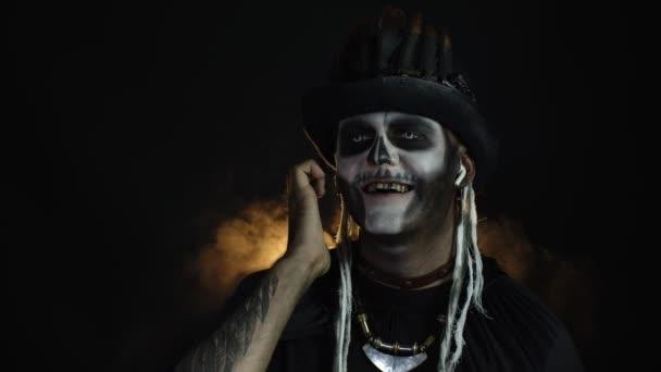 Strašidelný muž s kostrbatým make-upem v cylindru. Chlápek ve sluchátkách, poslouchá hudbu, tancuje