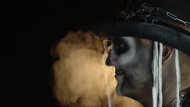 Děsivý muž v kostře Halloween make-up otočí hlavu a dívá se do kamery s očima široce otevřené