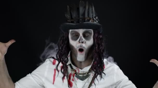 Zlověstný muž s halloweenskou kostrou make-up v košili s krví slaví, ukazující palce nahoru