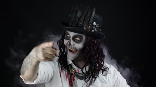 Gruselig lächelnder Mann im Skelett-Halloween-Kostüm im blutigen Hemd, der in die Kamera schaut und zeigt