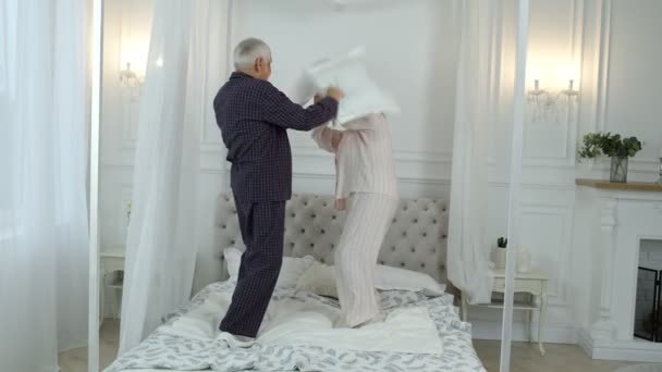 Active happy senior Caucasian grandparents couple jumping, having pillow fight on bed at home