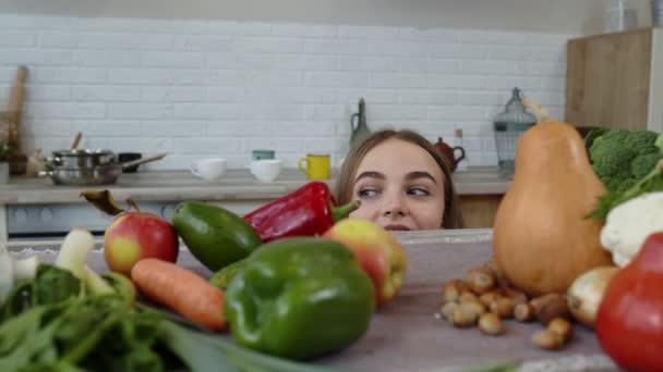Dívka nakukuje zpod stolu, krade čerstvé jablko a jí ho. Hubnutí, dietní koncept
