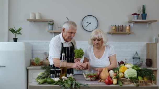 Ältere Großeltern in der Küche. Lustiger Opa scherzte über Oma. Sich einen Salat um den Kopf legen