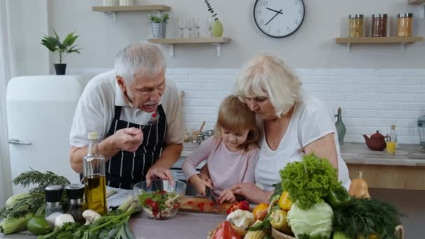 Senior couple in kitchen teaching granddaughter child how to cook, chopping pepper with knife