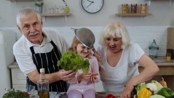 Seniorin und Mann mit Enkelin tanzen mit Sieb und Gemüse zu Hause