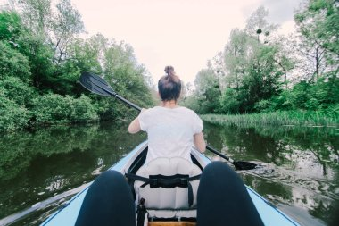 Two people are floating in a canoe on the river.