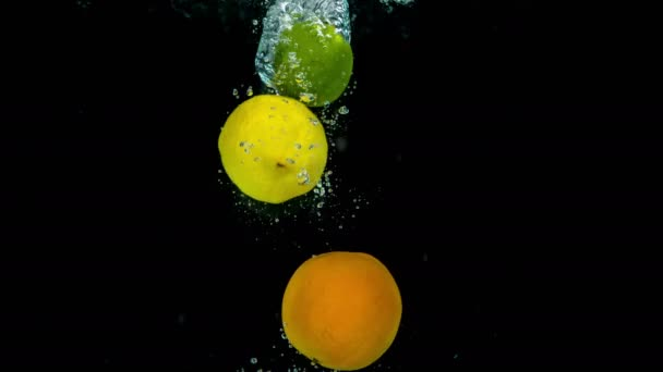 Trópusi sárga citromok és zöld lime esik kristálytiszta víz.