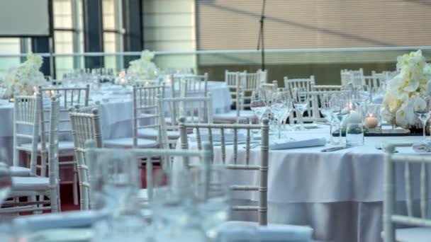 schön dekorierte runde Tische ganz in weiß und bereit für eine Geburtstagsfeier zu beginnen.