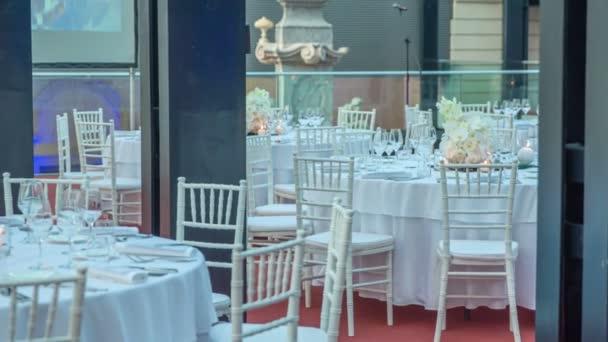 Runde Tische mit weißem, luxuriösem Strauß in der Mitte, umgeben von wunderschönem Ambiente. Die Szene ist bereit für eine rauschende Hochzeitsfeier.