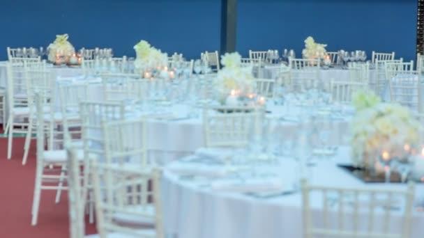 viele runde Tische schön in weiß dekoriert warten darauf, dass die besondere Hochzeitsfeier beginnt.