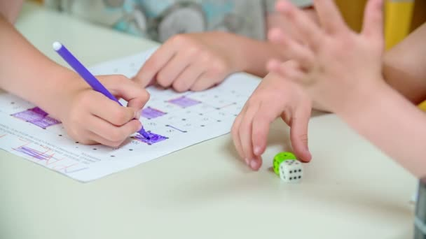 Two kids are playing with two dice and and they are writing something on paper. They are playing a game.